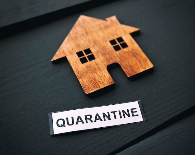"""Mały drewniany dom i transparent z napisem """"kwarantanna"""" na stole. pojęcie kwarantanny koronawirusa"""