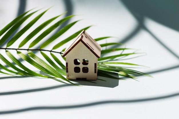 Mały drewniany dom na białym tle z cieniem