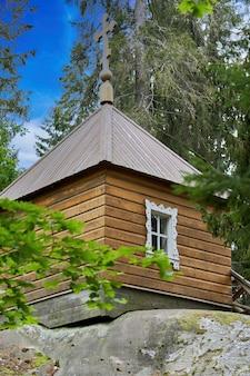 Mały drewniany dom na dużym kamieniu w lesie. zaciszne mieszkanie leśniczego
