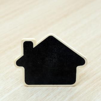 Mały drewniany dom na stole. koncepcja dla firm z branży nieruchomości.