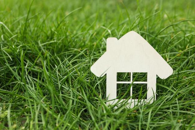 Mały drewniany dom na zielonej trawie. kupno nieruchomości
