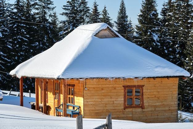 Mały drewniany dom pokryty świeżym opadłym śniegiem, otoczony wysokimi sosnami w zimowych górach.