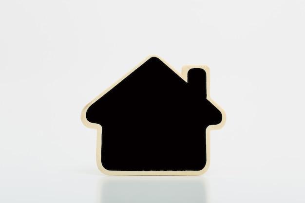 Mały drewniany dom z czarnym puste na stole. koncepcja dla firm z branży nieruchomości.