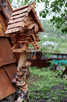 Mały drewniany domek na drzewie. ozdobny karmnik dla ptaków wykonany z drewna