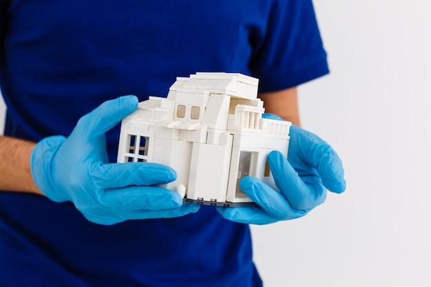 Mały drewniany domek w dłoni z białą gumową rękawicą medyczną, niebieskie tło, drewniany model domu, koncepcja kwarantanny, pandemia koronawirusa, medycyna w czasie epidemii