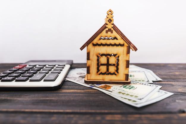 Mały drewniany domek z kalkulatorem i dolarami, koncepcja kupna mieszkania, wynajmu lub zastawu