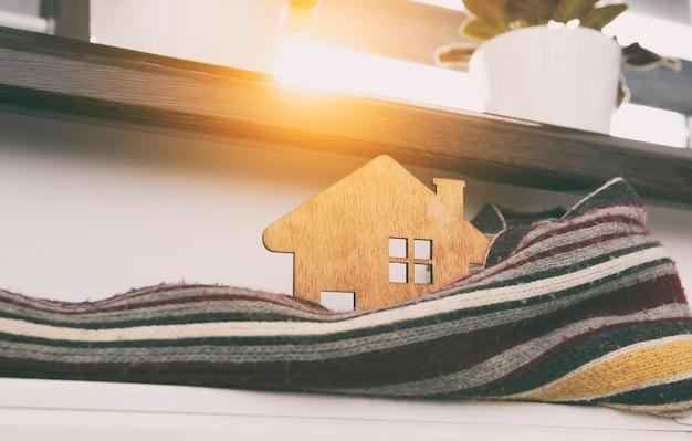 Mały drewniany domek zawinięty w szalik leżący na kaloryferze w domu