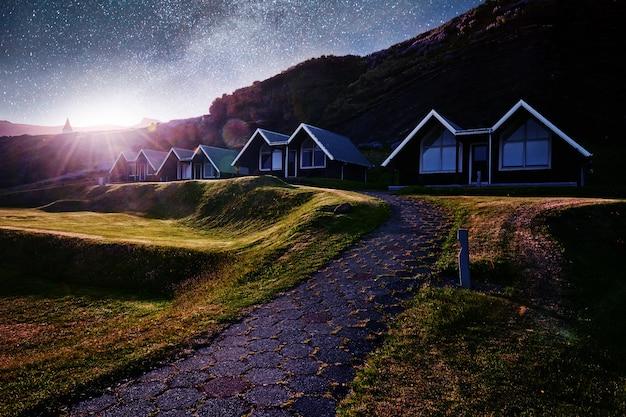 Mały drewniany kościół i cmentarz hofskirkja hof, skaftafell islandia. malowniczy zachód słońca przez korony drzew