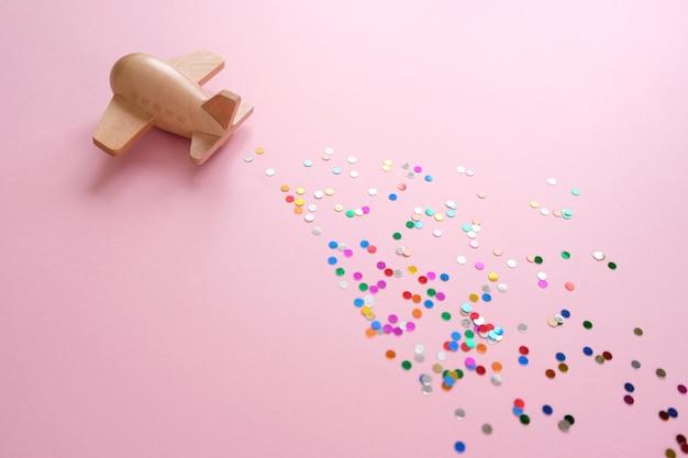 Mały drewniany zabawkowy samolot szczęścia przez konfetti