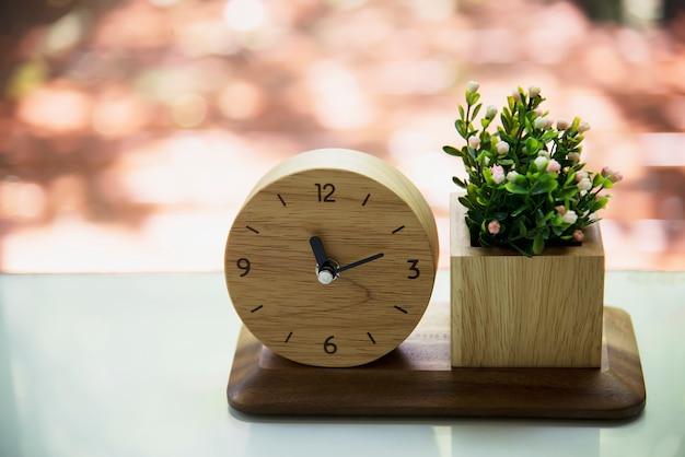 Mały drewniany zegar z dekorowanym zestawem kwiatowym
