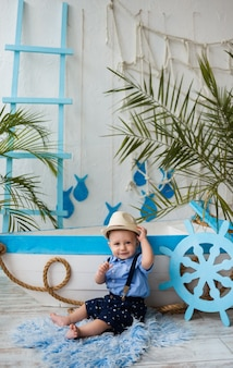 Mały dżentelmen w słomkowym kapeluszu siedzi przy drewnianej łodzi
