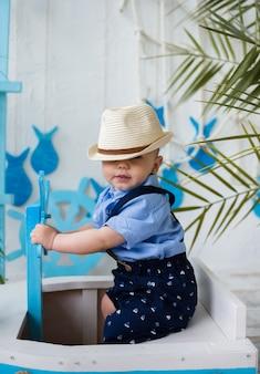 Mały dżentelmen w słomkowym kapeluszu siedzi w drewnianej łodzi przy powierzchni z morskimi dekoracjami