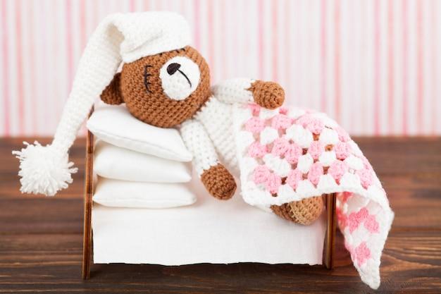 Mały dzianinowy miś w piżamie i śpiwór śpi z poduszkami. amigurumi. wykonany ręcznie. ciemne drewniane tła
