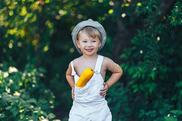 Mały dzieciak rolnik ubrany w białe szaty śmiejąc się z żółtym kabaczek, żniwa