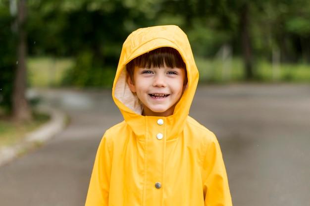 Mały dzieciak uśmiechnięty w płaszcz przeciwdeszczowy