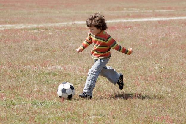 Mały dziecko bawić się futbol w polu