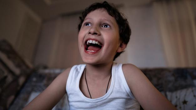 Mały emocjonalny chłopiec, szczęśliwy z szerokim uśmiechem, ogląda późno w nocy telewizję