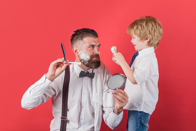 Mały fryzjer. koncepcja fryzjera. salon dla mężczyzn. wyglądaj idealnie w salonie fryzjerskim. asystent dla taty. dzień ojca. golenie brody u fryzjera. pielęgnacja brody.
