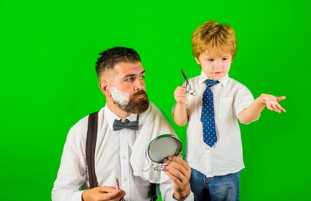 Mały fryzjer syn i tata asystent golenia brody dla koncepcji taty fryzjera dzień ojca dzień rodziny