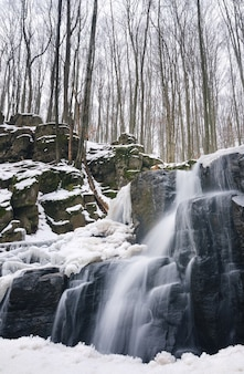 Mały górski wodospad jest pokryty śniegiem. strumień w lesie, zimowy krajobraz, jasne tło