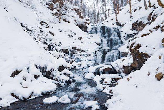 Mały górski wodospad lodowatej wody płynącej wśród mokrych kamieni pokrytych białym śniegiem