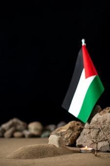 Mały grób z flagą palestyńską i kamieniami na ciemnej powierzchni