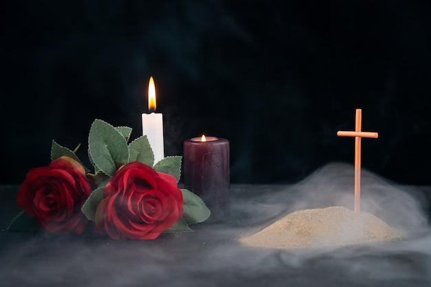 Mały grób ze świecami i kwiatami jako wspomnienie na ciemnej powierzchni
