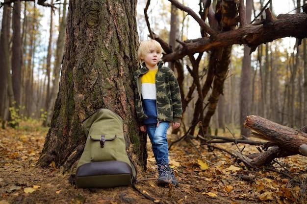 Mały harcerz z dużym plecakiem odpoczywa w pobliżu dużego drzewa w dzikim lesie w jesienny dzień.