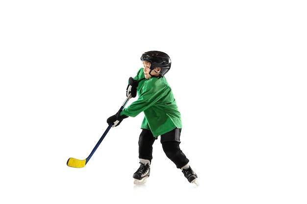 Mały hokeista z kijem na boisku, białe studio tło. sportsboy noszący sprzęt i kask, ćwiczący, trenujący. pojęcie sportu, zdrowego stylu życia, ruchu, ruchu, akcji.