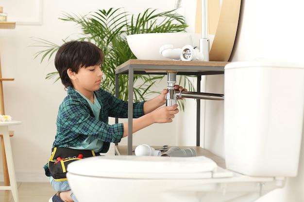 Mały hydraulik naprawiający zlew w toalecie