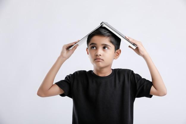 Mały indyjski / azjatycki chłopiec z książką na głowie i poważnie myślący