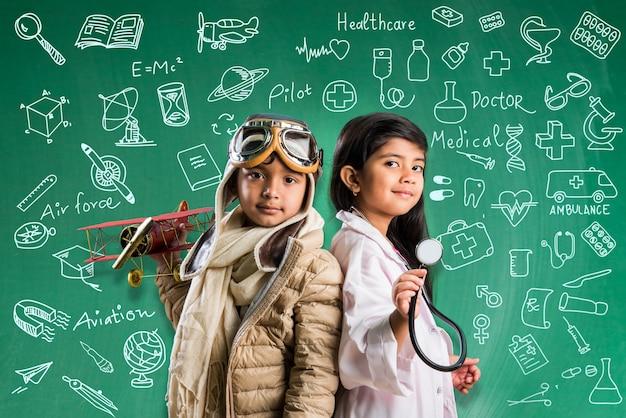 Mały indyjski chłopiec i dziewczynka pozują przed zieloną tablicą kredową w przebraniu pilota i stroju lekarza ze stetoskopem