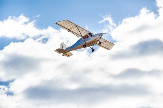 Mały jednosilnikowy samolot lecący nad głową na tle błękitnego nieba