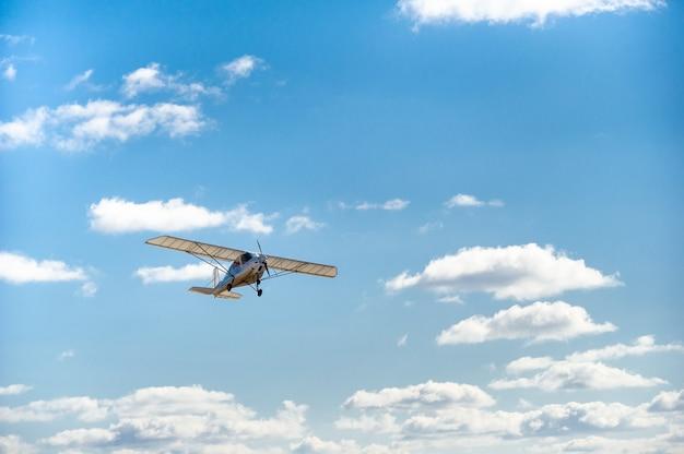 Mały jednosilnikowy samolot lecący nad głowami na tle błękitnego nieba