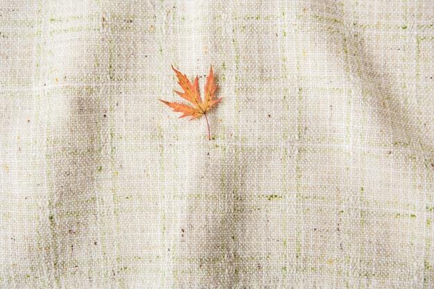 Mały jesienny liść. leżał na płasko. tło obrus. minimalistyczny styl.