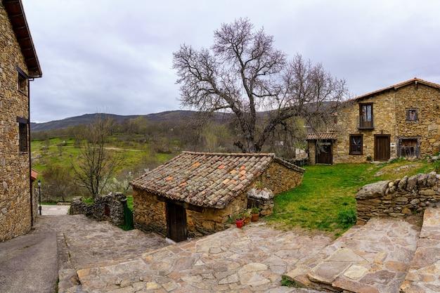 Mały kamienny dom na starym mieście z typowymi kamiennymi domami i schodami w alei. horcajuelo madrid. hiszpania.