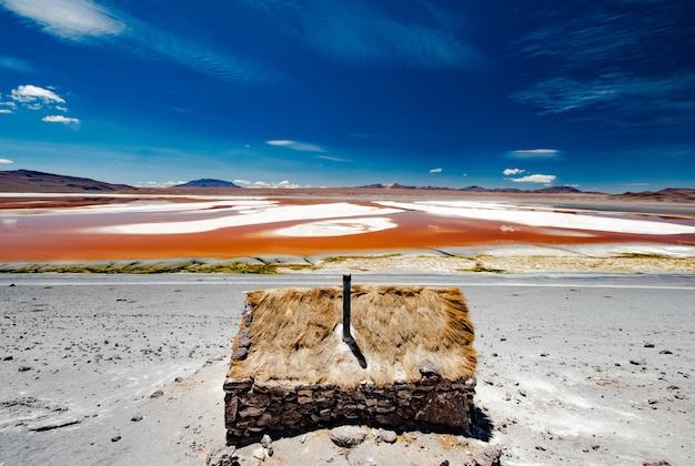 Mały kamienny dom w pobliżu szerokiej laguny colorado w boliwii