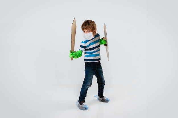 Mały kaukaski chłopiec jako wojownik w walce z pandemią koronawirusa, atakujący z tarczą, włócznią i bandolą z papieru toaletowego, atakujący