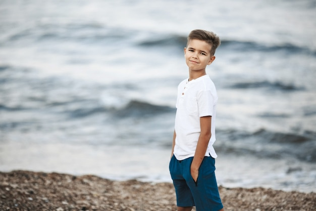 Mały kaukaski chłopiec stoi na plaży w pobliżu falującego morza w białej koszulce i niebieskich szortach