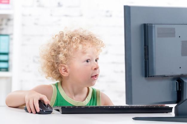 Mały kędzierzawy blond chłopiec bawi się komputerem