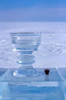 Mały kieliszek z czerwonym trunkiem i duży kubek na lód stoją na tle białego śniegu. miska i nalewka stoją na lodowym talerzu. pionowy.