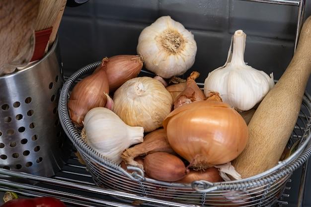 Mały kosz w kuchni obok naczyń z czosnkiem, cebulą i szalotką.