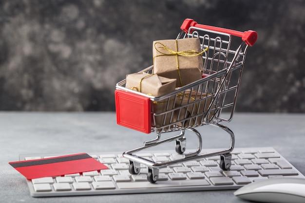 Mały koszyk z prezentami i kartą kredytową na klawiaturze laptopa