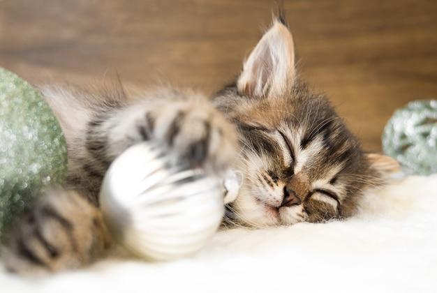 Mały kotek śpi na białym miękkim kocu z bombkami.