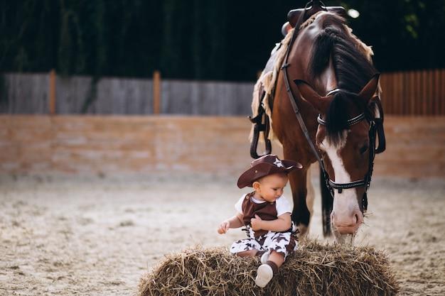 Mały kowbojski obsiadanie na sianie