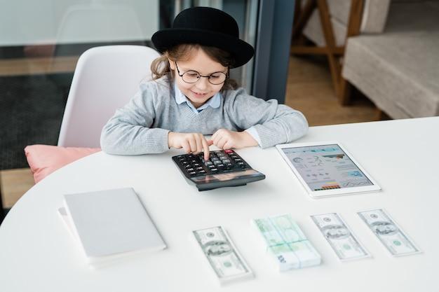 Mały księgowy korzystający z kalkulatora przy liczeniu pensji lub pieniędzy i przeprowadzaniu analiz finansowych przy biurku