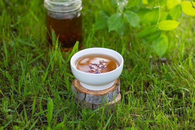 Mały kubek i szklany imbryk herbaty ziołowej z kwiatami w ogrodzie wśród trawy i zielonych liści na drewnianym stojaku