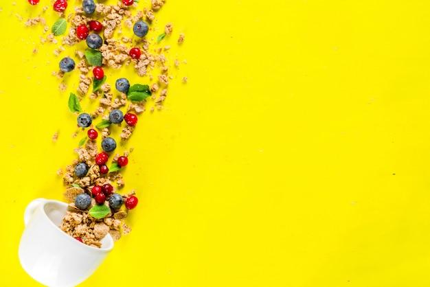 Mały kubek ze śniadaniową muesli, orzechami i jagodami