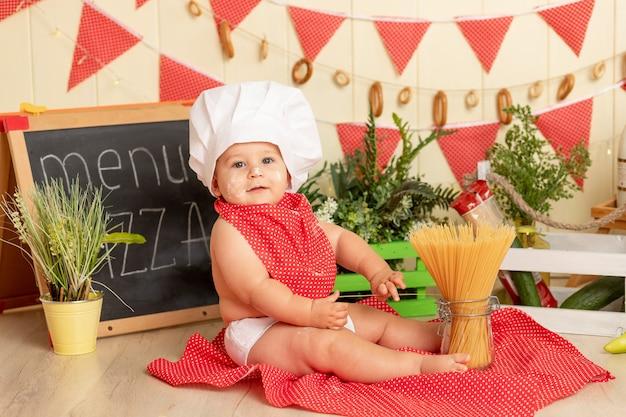 Mały kucharz, małe dziecko w czapce szefa kuchni gotuje spaghetti w kuchni