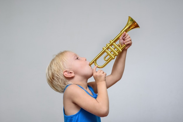 Mały ładny blond chłopiec grający zabawkową trąbkę na lekkiej ścianie